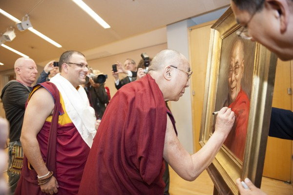 His Holiness the Dalai Lama signing a portrait done by artist Leo Mancini-Hresko